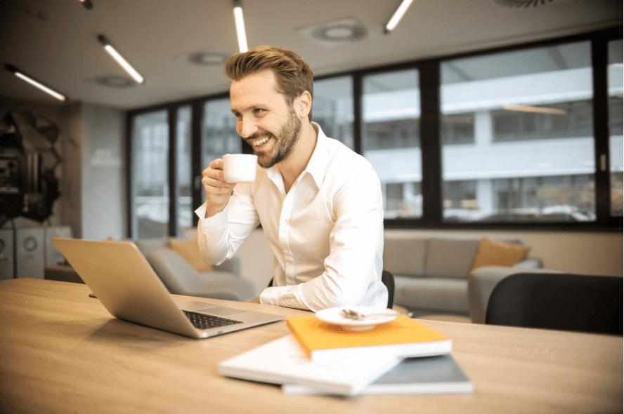 Homem em um escritório bebendo café e sorrindo